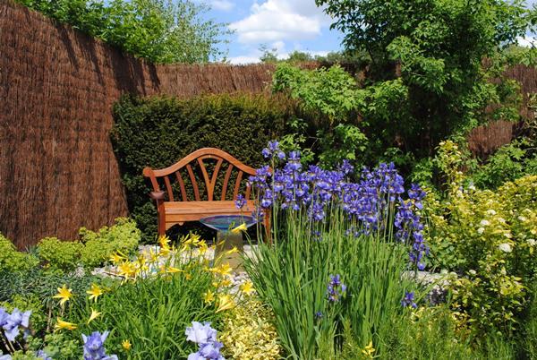 jardín con flores y banco de madera